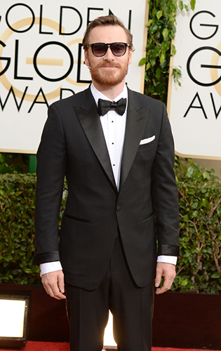 Michael Fassbender in a black tie tuxedo with sunglasses.