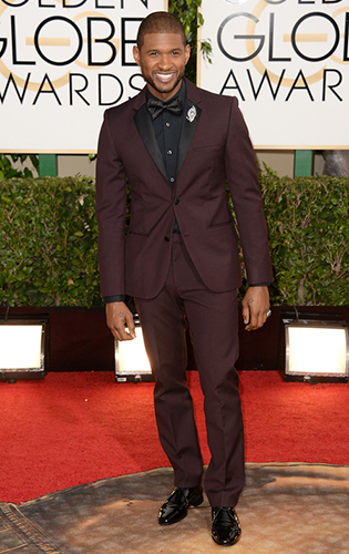 Usher in a burgundy tuxedo with black shirt, bow tie, and brooch.